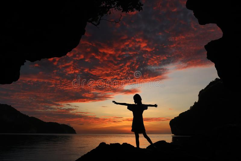 Silhouette girl standing and stretch the arms on the rocks red s royalty free stock photography
