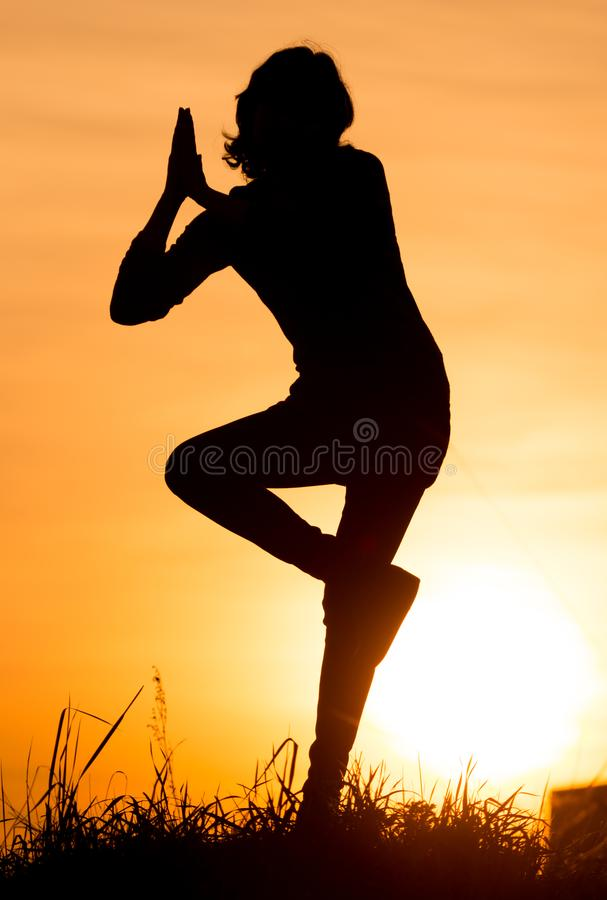 Silhouette of a girl in the sunset stock image