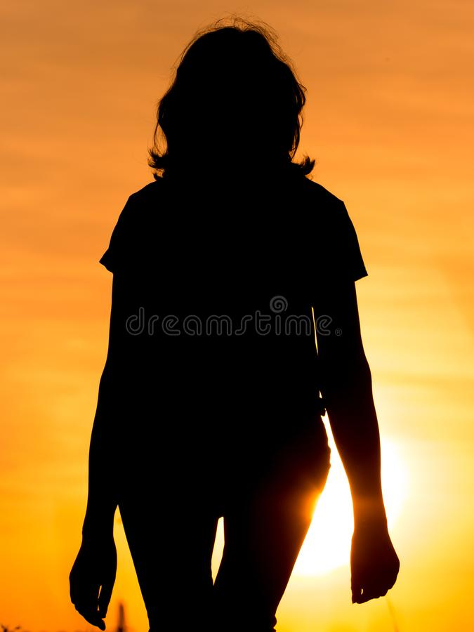 Silhouette of a girl in the sunset stock photography