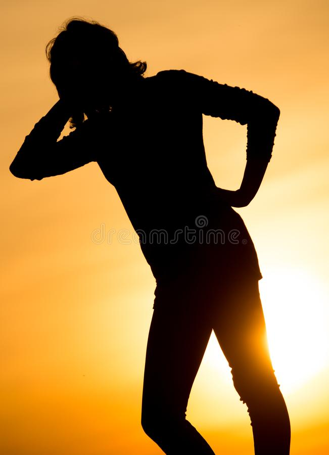 Silhouette of a girl in the sunset stock photo