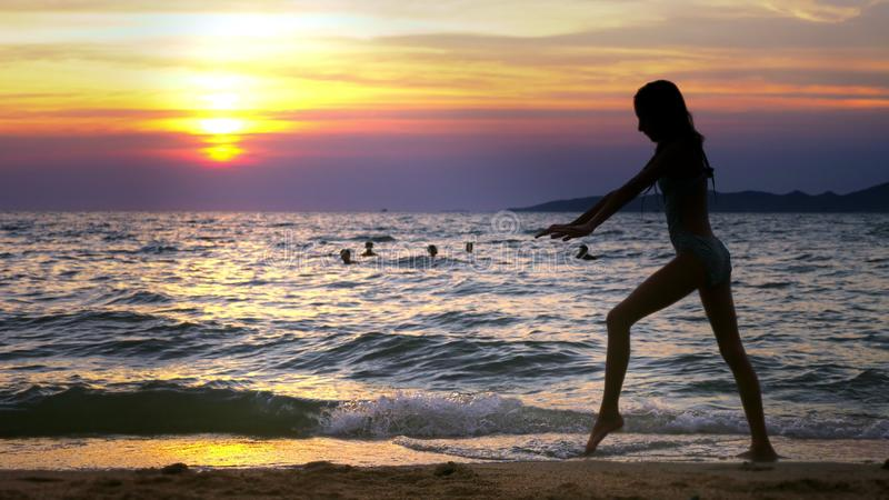 Silhouette of a girl at sunset, against the background of the sea, slender leggy girl funny doing gymnastic coups on the royalty free stock photography