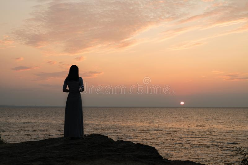 Silhouette of a girl on a sunset background sunrise on the sea. Horizon line. Summer walk on the beach stock photography