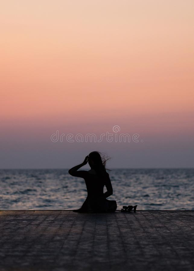 Silhouette of a girl on a sunset background sunrise on the sea. Horizon line. Summer walk on the beach stock image