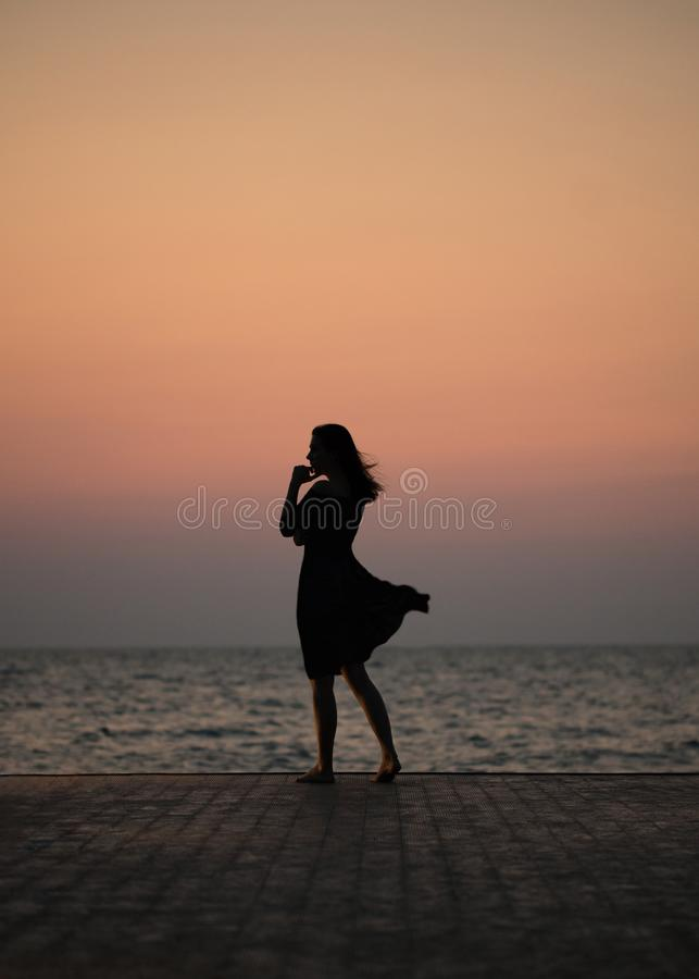 Silhouette of a girl on a sunset background sunrise on the sea. Horizon line. Summer walk on the beach royalty free stock images