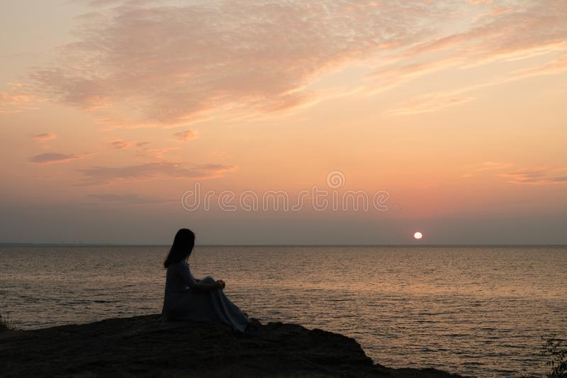 Silhouette of a girl on a sunset background sunrise on the sea. Horizon line. Summer walk on the beach stock images