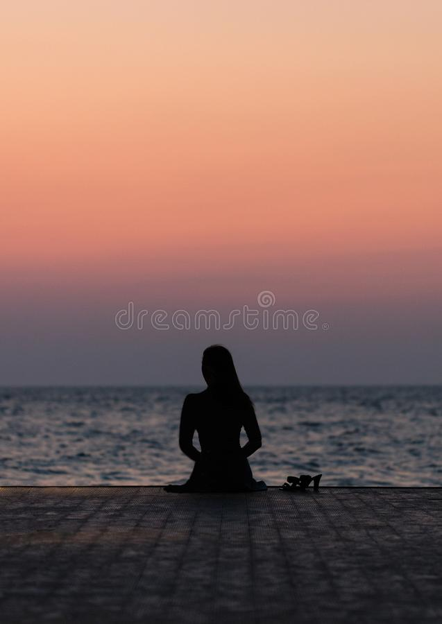 Silhouette of a girl on a sunset background sunrise on the sea. Horizon line. Summer walk on the beach royalty free stock image