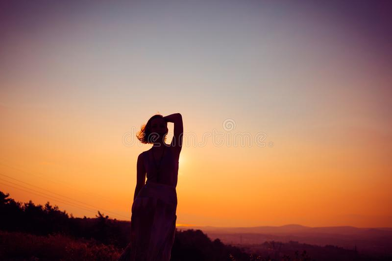 Silhouette of a girl at sunset royalty free stock photos