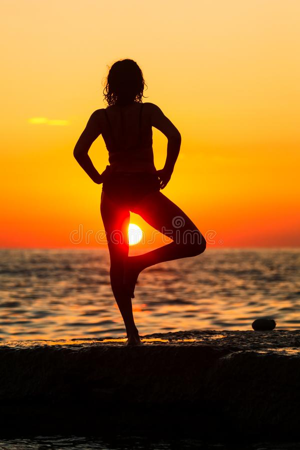 Silhouette of a girl at sunset on the sea royalty free stock images