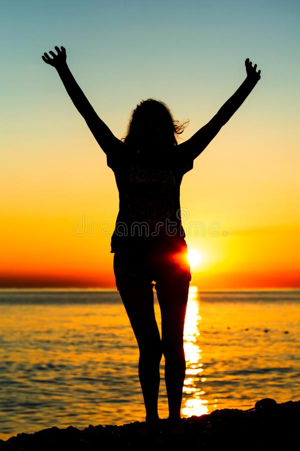 Silhouette of a girl at sunset on the sea stock images