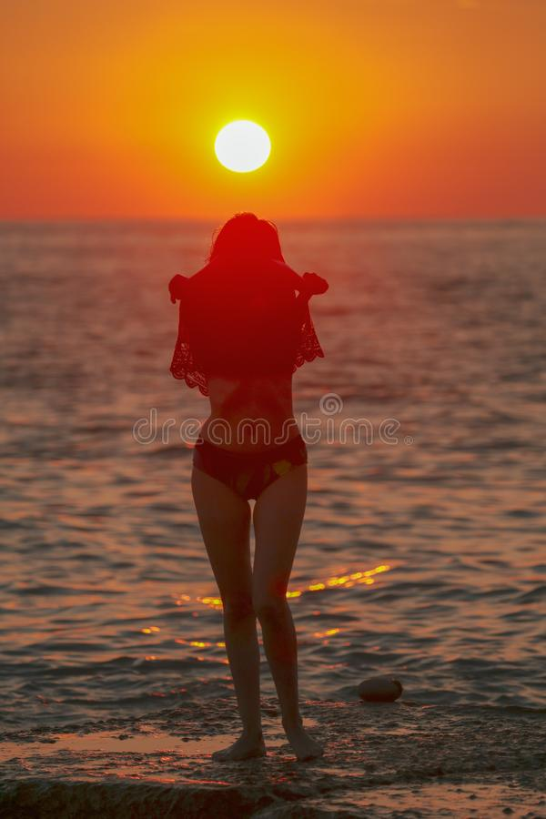 Silhouette of a girl at sunset on the sea stock photo
