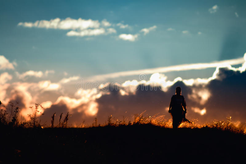 Silhouette of a girl walking in the sunset royalty free stock photo