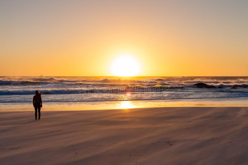 Silhouette girl watching a sunset on a sandy beach with rough ocean wind. stock image