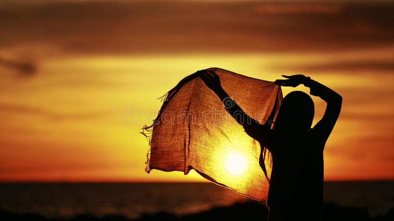 Silhouette of a girl wearing hijab dancing during sunset stock photos