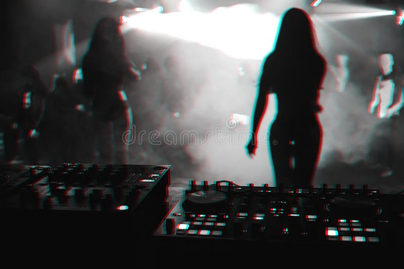 Silhouette girls dancers on stage in nightclub on background music the mixer DJ. Silhouette girls dancers on stage in a nightclub on the background music the royalty free stock photo