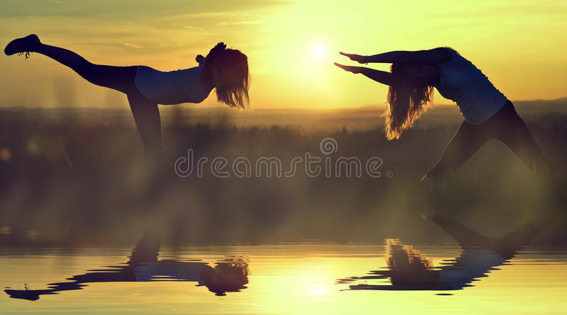 Silhouette girls stretching on a meadow royalty free stock photos