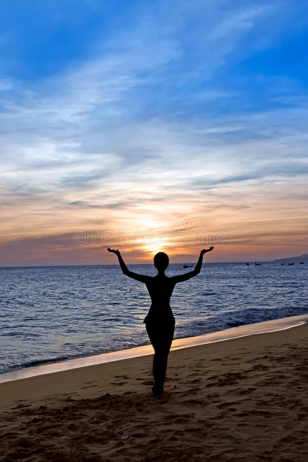 Silhouette graceful woman on the sunset. Silhouette young beautiful woman on a beach. Sunset royalty free stock images