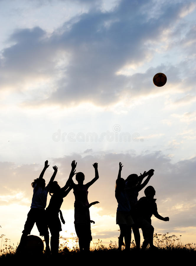 Silhouette, group of happy children. Playing on meadow, sunset, summertime royalty free stock images