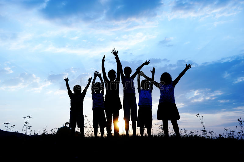 Silhouette, group of happy children. Playing on meadow, sunset, summertime royalty free stock photos