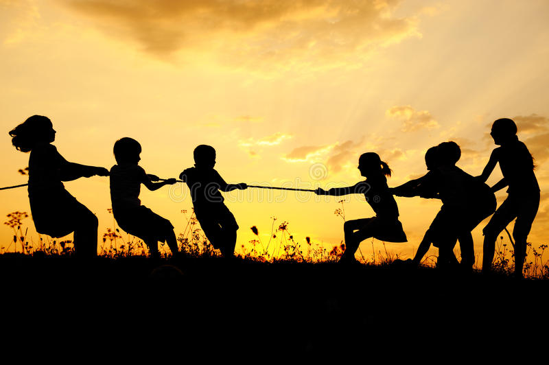Silhouette, group of happy children. Playing on meadow, sunset, summertime royalty free stock photo