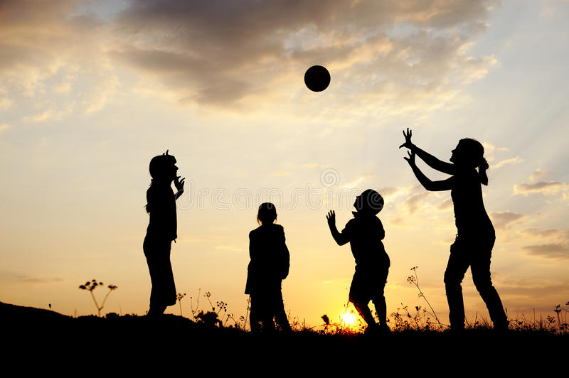 Silhouette, group of happy children. Playing on meadow, sunset, summertime stock photography