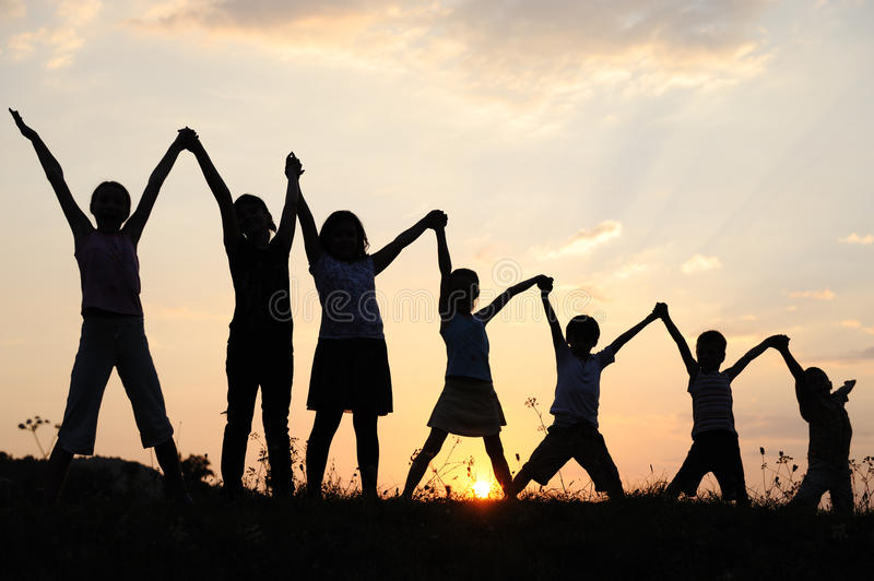 Silhouette, group of happy children. Playing on meadow, sunset, summertime royalty free stock photography