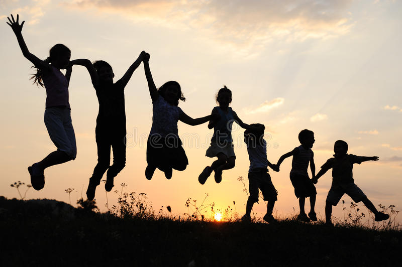 Silhouette, group of happy children. Playing on meadow, sunset, summertime stock image