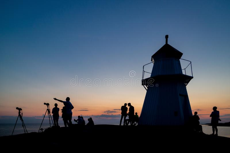 Silhouette of a group of people gathering to view the lunar eclipse stock image