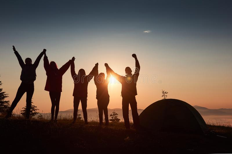 A silhouette of group people have fun at the top of the mountain near the tent during the sunset stock images