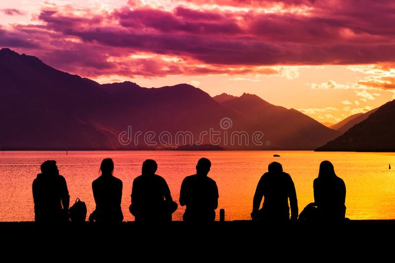 Silhouette Group of Young People Sitting on Beach. Silhouette group of young people sitting on lake beach against mountain landscape at sunset showing concept of stock photos
