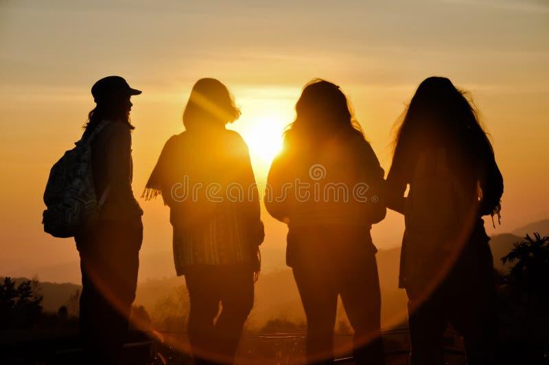 Silhouette-gruppen resande ser solnedgången på berget i lyckliga tider känna sig avslappnad i livsstilen arkivfoto