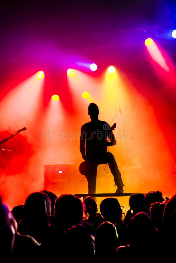 Silhouette of guitar player in action on stage stock images