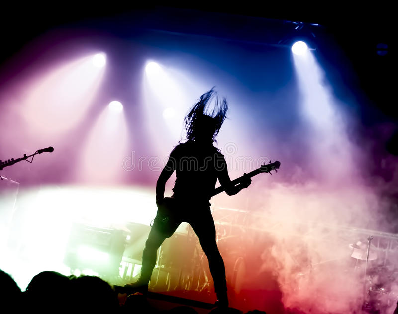 Silhouette of guitar player in action on stage royalty free stock photo