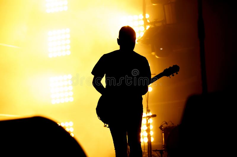 Silhouette of guitar player, guitarist perform on concert stage. Orange background, smoke, concert spotlights royalty free stock photo