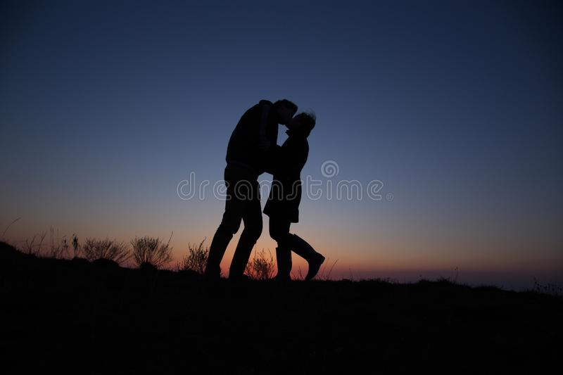 Silhouette guy and girl on a beautiful sunset royalty free stock images