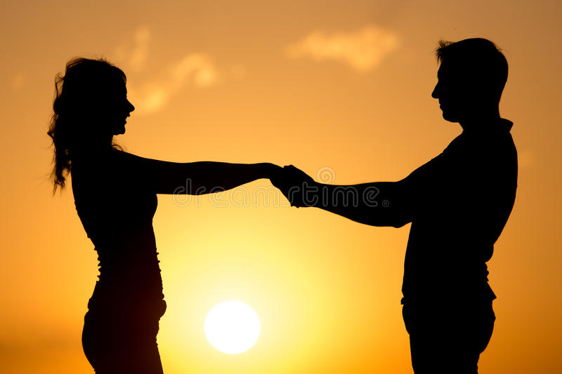 Silhouette of a guy and a girl at sunset stock photo