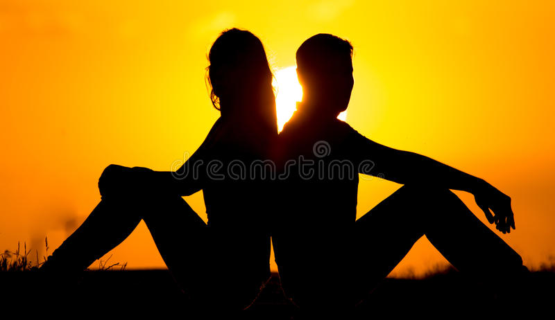 Silhouette of a guy and a girl at sunset royalty free stock images