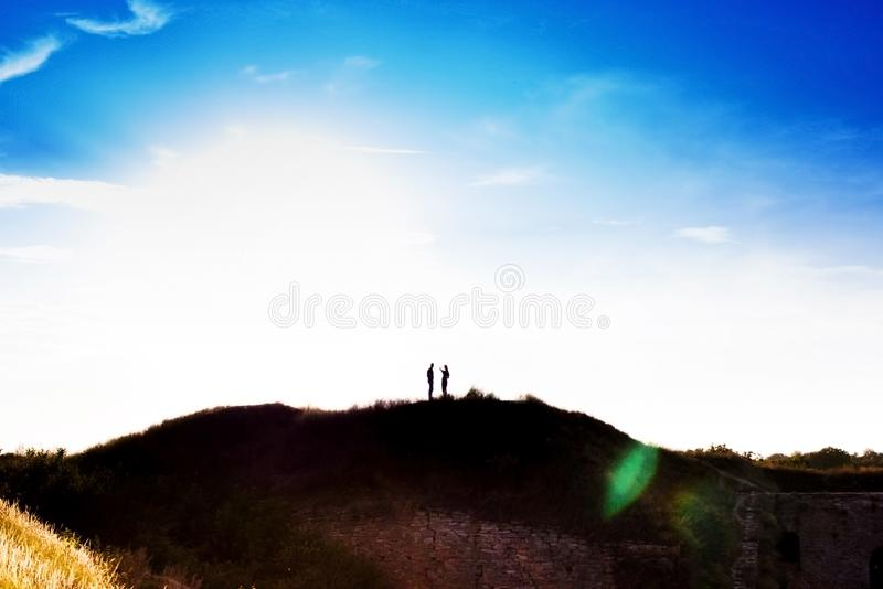 Silhouette of a guy and a girl who hold hands on a mountain on a background of the sea and sunset sunset royalty free stock photo
