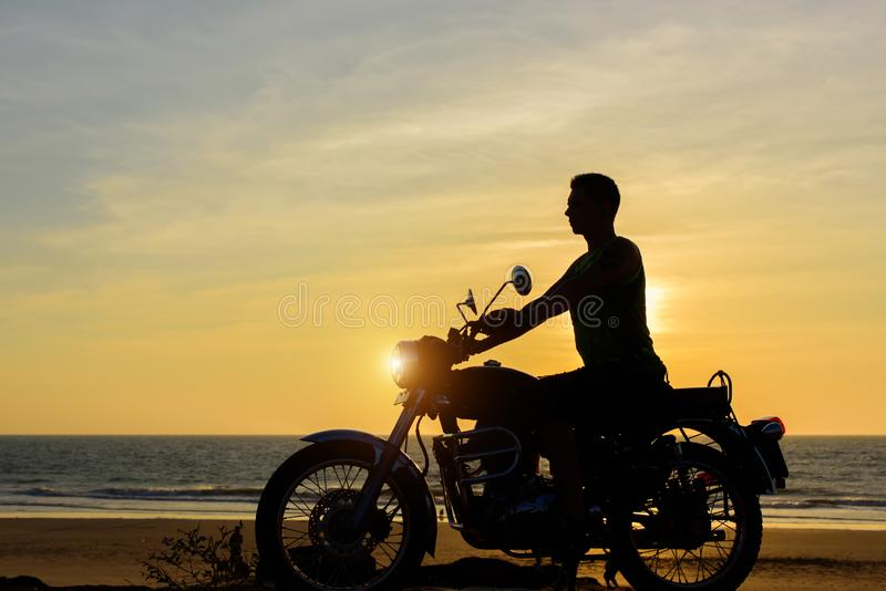Silhouette of guy on motorcycle on sunset background. Young biker are sitting on motorcycle, face in profile. Moto trip royalty free stock image