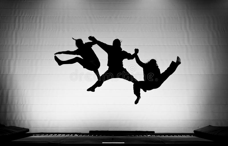 Silhouette of gymnasts on trampoline stock images