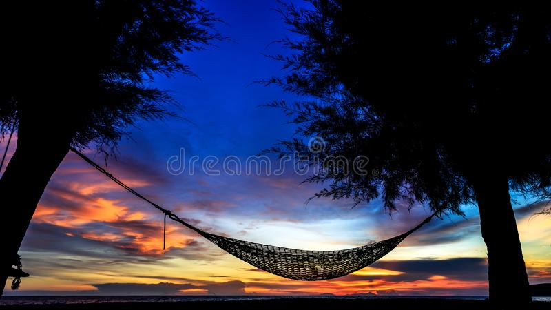 Silhouette of Hammock suspended between two trees on the beach with beautiful sunset sky royalty free stock image