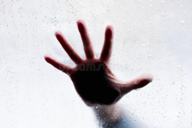 Silhouette of hand behind glass stock image