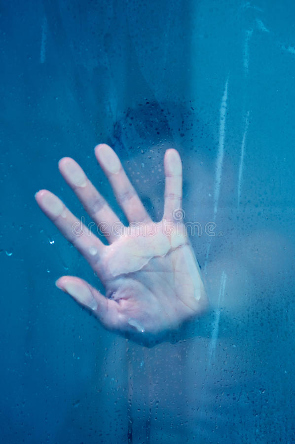 Silhouette of hand behind glass stock photos