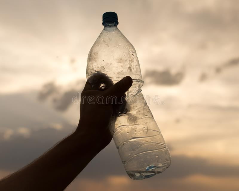 Silhouette hand with a bottle on a sunset background stock image