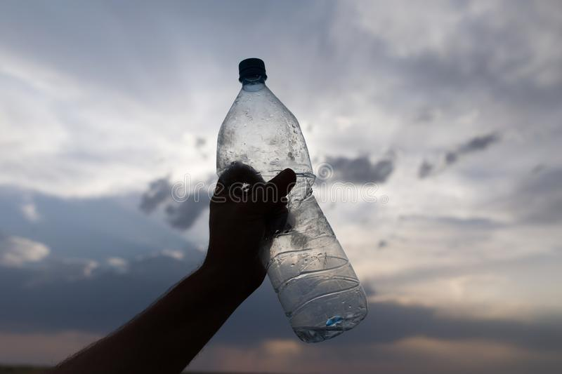 Silhouette hand with a bottle on a sunset background royalty free stock photography