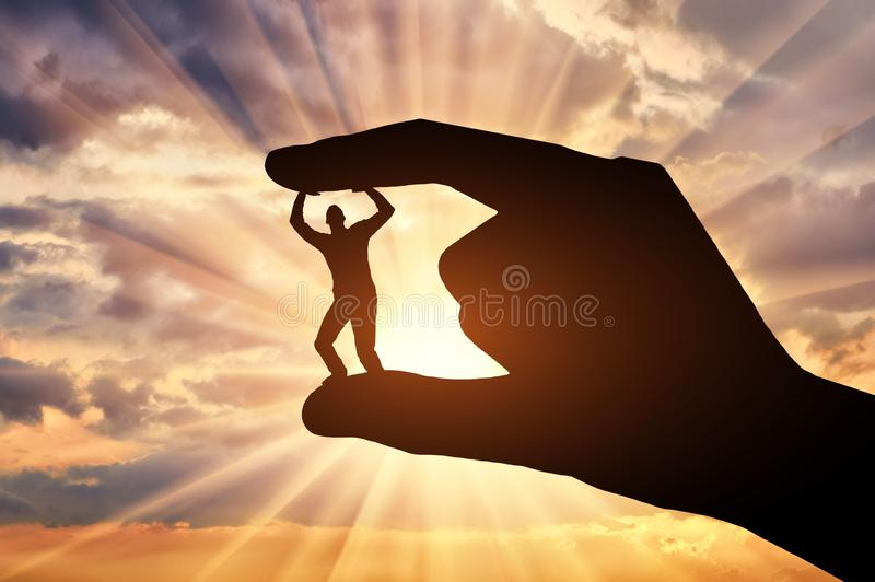 Workplace bullying. Silhouette of a hand holds between the fingers a man. Silhouette of a hand holds between the fingers a man against the sunset. Workplace stock photos