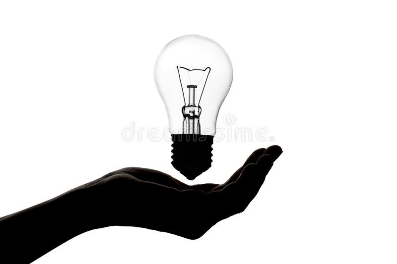 Silhouette of hand with an incandescent lamp, thought bulb, concept of idea on white isolated background. Silhouette of a woman`s hand with an incandescent lamp royalty free stock photo