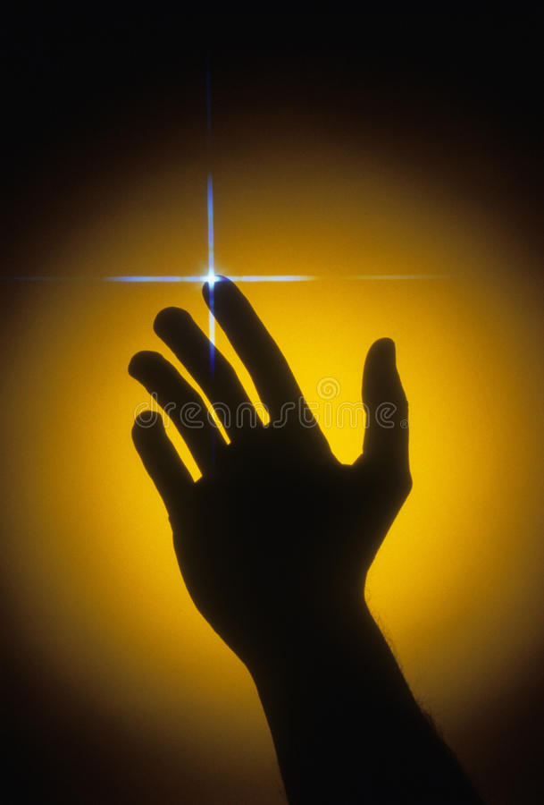 Silhouette of Hand With Light Burst. A hand surrounded by a yellow glow with a burst of light on the fingertip. Vertical shot royalty free stock photo