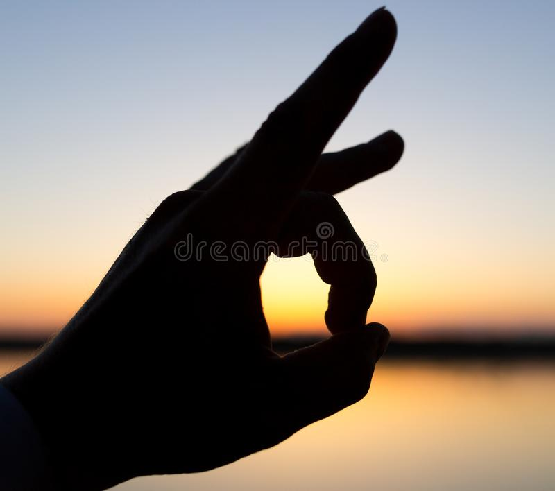 Silhouette of the hand on the sunset background stock image