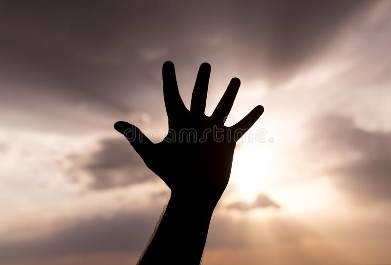 Silhouette of the hand on the sunset background royalty free stock photography