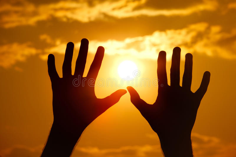 Silhouette of hands against the orange sunset. royalty free stock photo